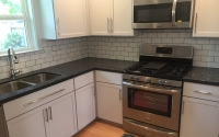 Quartz counters, custom cabinets, backsplash and stainless steel appliances